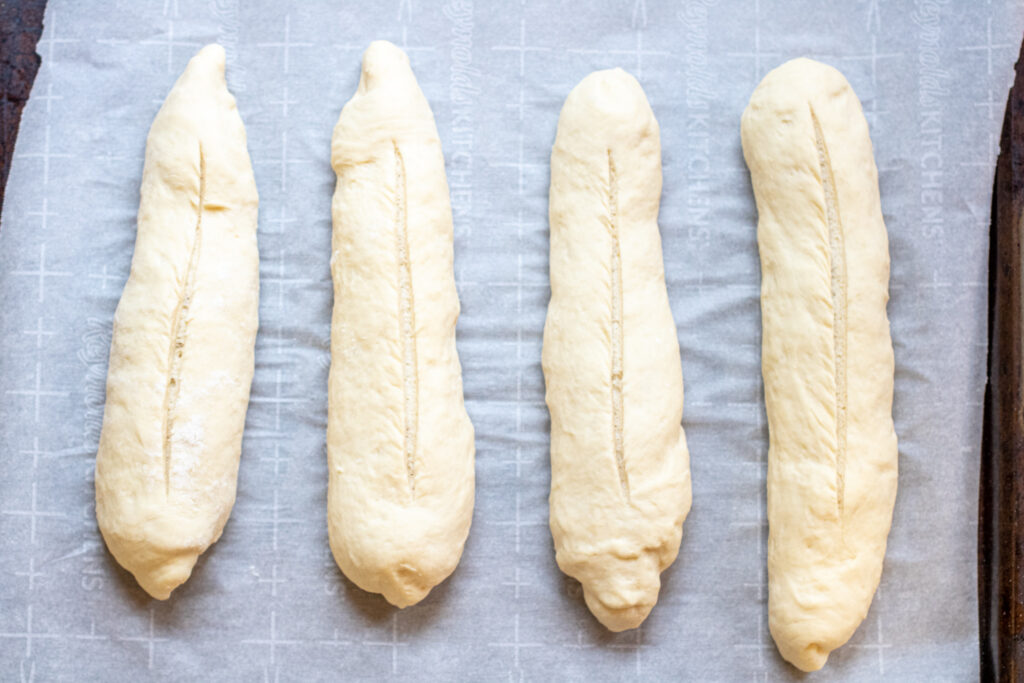 baguette dough shaped and scored