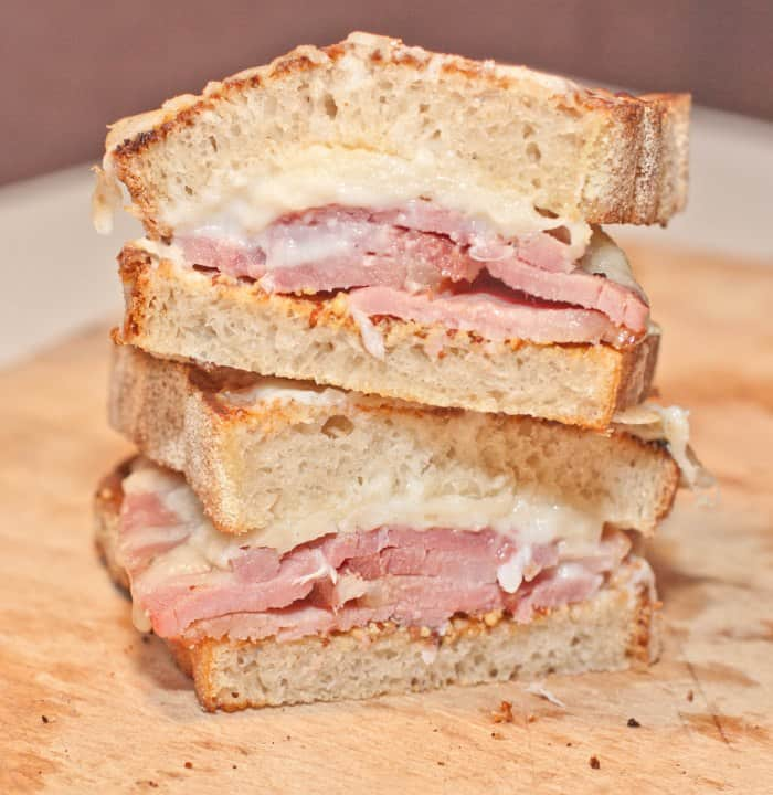 stacked ham and cheese sandwich sliced in half.
