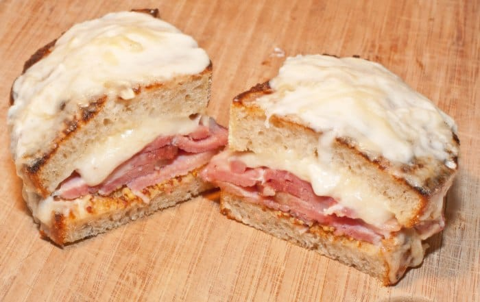two halves of ham and cheese topped with melted cheese.