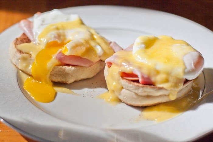 a plate with eggs benedict with hollandaise sauce.