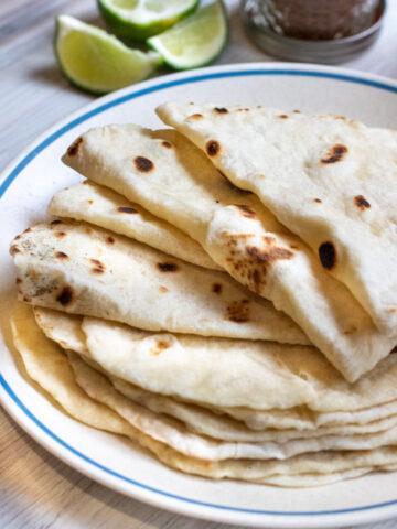 a plate of folded flour tortillas.