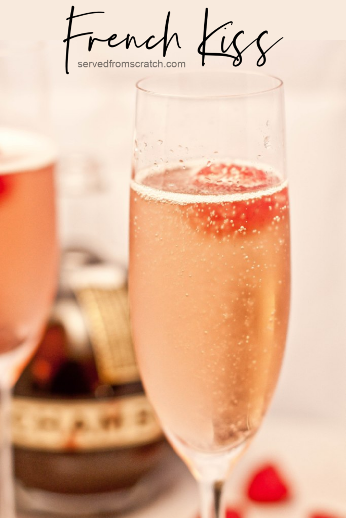 a champagne flute with a pink bubbly drink and a raspberry