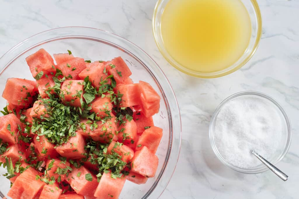 diced watermelon in a bowl with mint next to two bowls