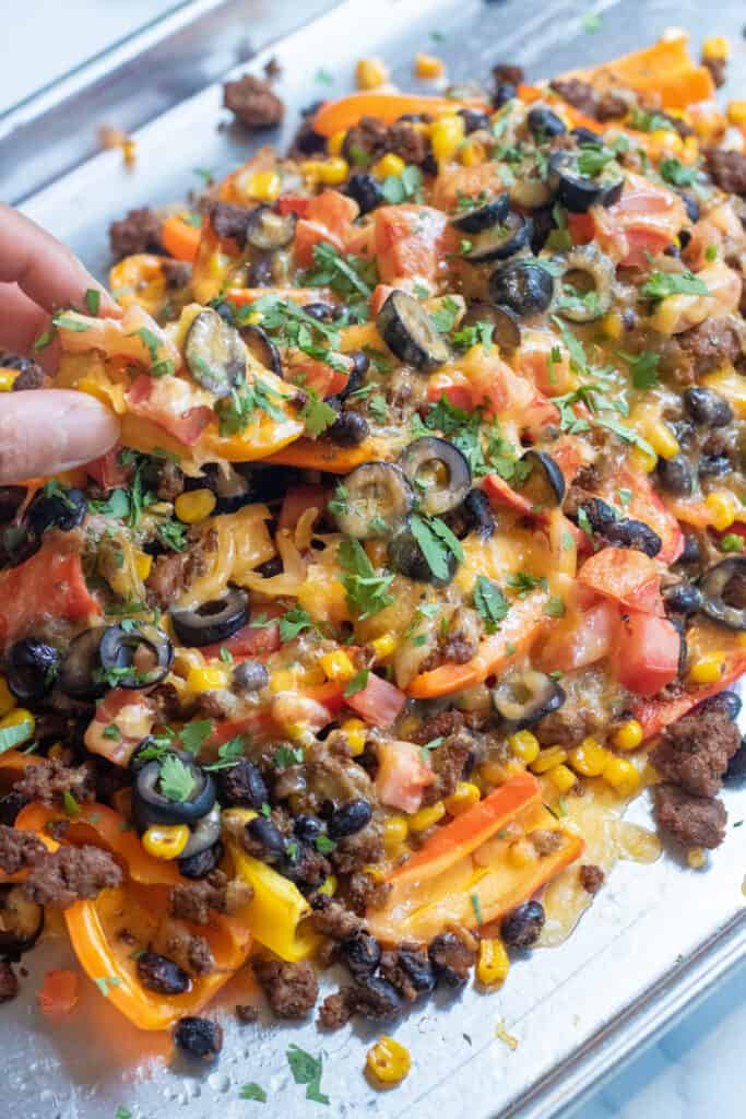 a baking sheet of mini peppers with ground beef, olives, black beans, corn, melted cheese, and fresh cilantro nachos.
