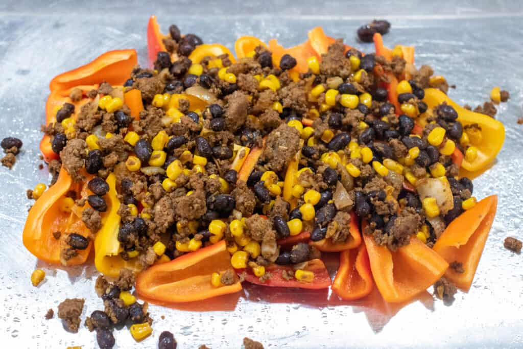 mini peppers topped with meat and beans and corn, tomatoes, and olives.