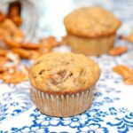 banana pecan muffin on table surrounded by pecans