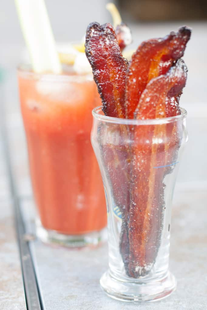 cup of candied bacon in front of a bloody mary