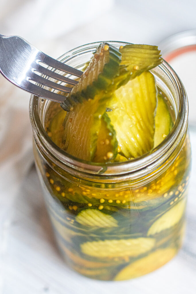 a large jar of pickles with a fork spearing some out.