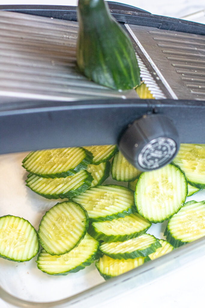 a cucumber being sliced on a mandolin and cucumber slices.