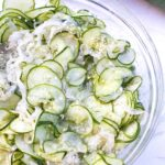 cucumbers, onions and sesame seeds in a bowl.