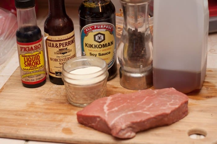 steak on cutting board with spices and seasonings behind it.