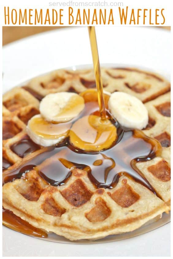 cooked banana waffles on a plate topped with bananas and maple syrup poured