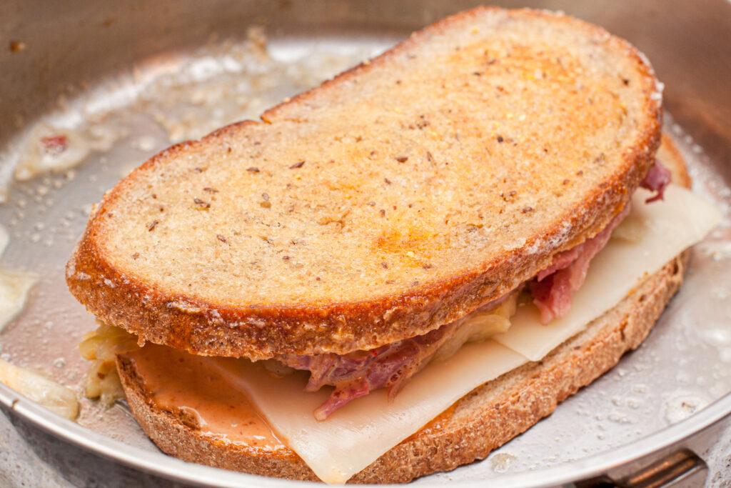 a rye bread sandwich grilling in a pan