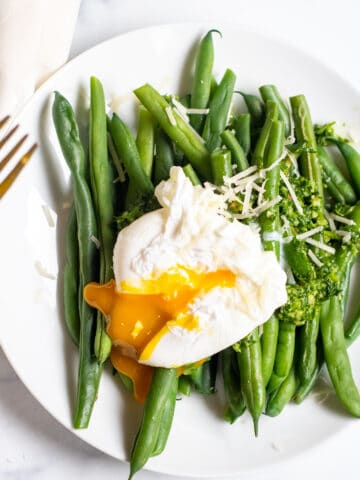 two plates with green beans and pesto and topped with a runny poached egg.