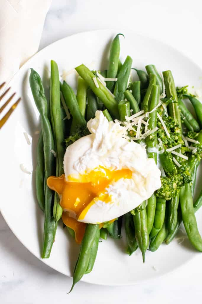 a plate with green beans and pesto and topped with a runny poached egg.
