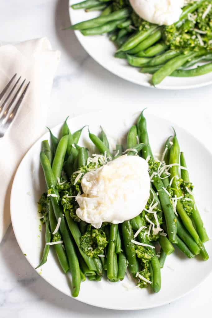 two plates with green beans and pesto and topped with a poached egg.