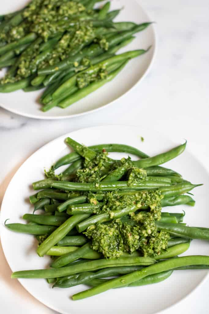 two plates with green beans and pesto.