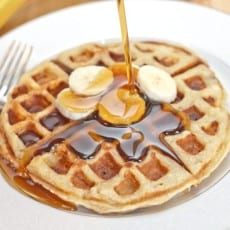 cooked banana waffles topped with sliced bananas and syrup