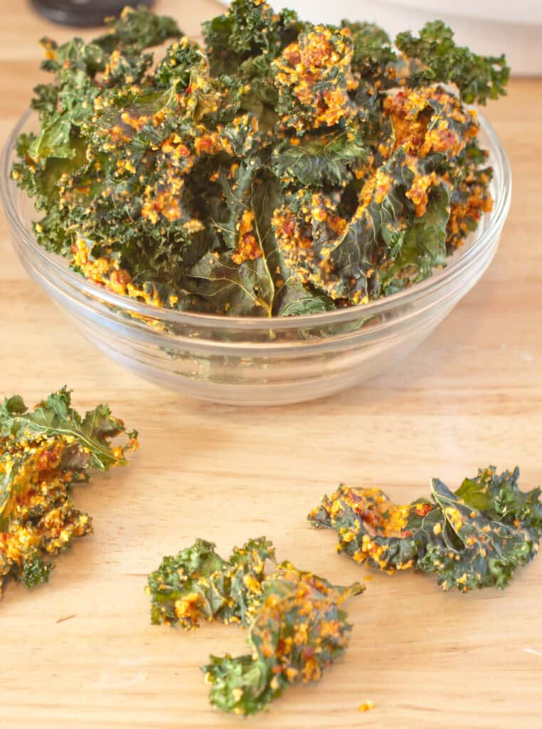 a bowl with coated kale chips and a few on the counter.