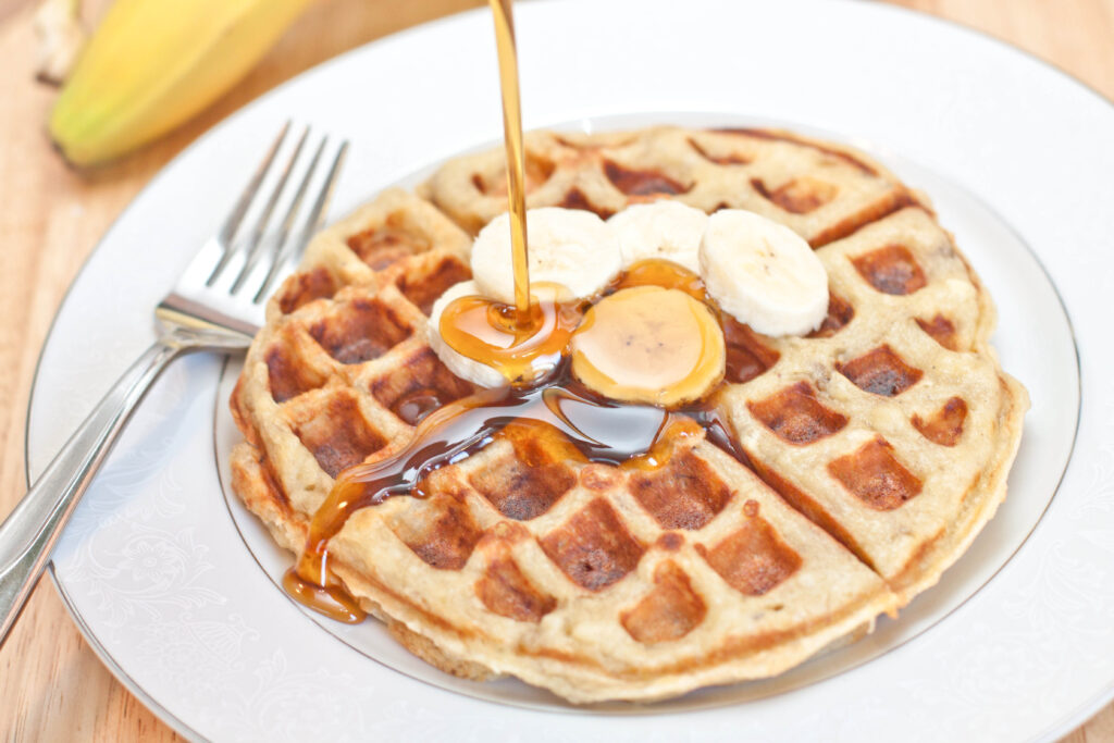 a round waffle on a plate with sliced bananas and syrup being poured on top.