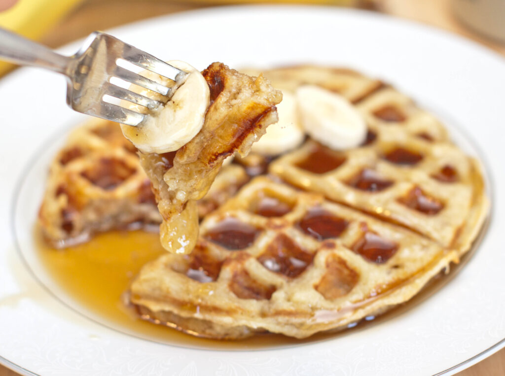 a banana waffle with syrup and a fork holding up a bite.