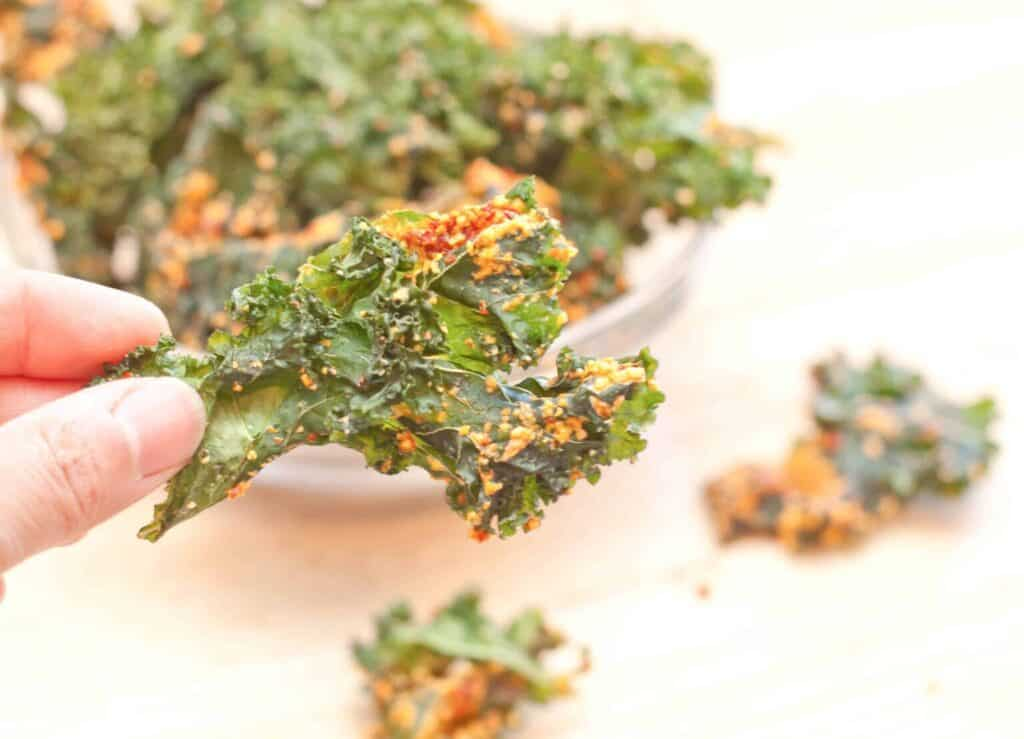 a hand holding a kale chip with cashews and sundried tomatoes.