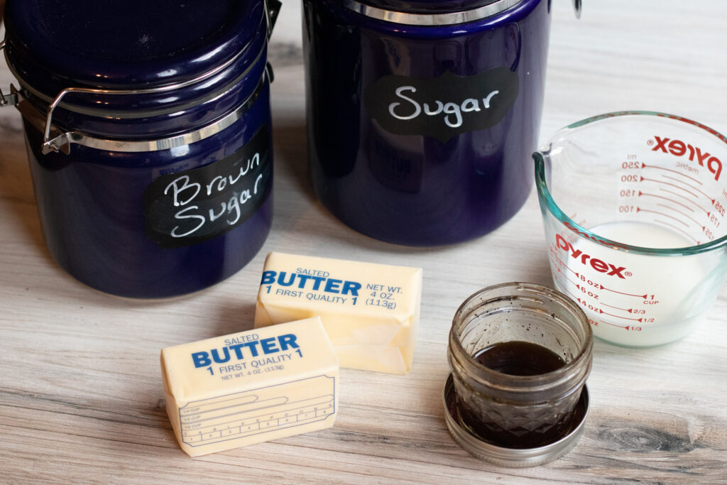 sugar containers, butter, vanilla extract, and milk on counter.