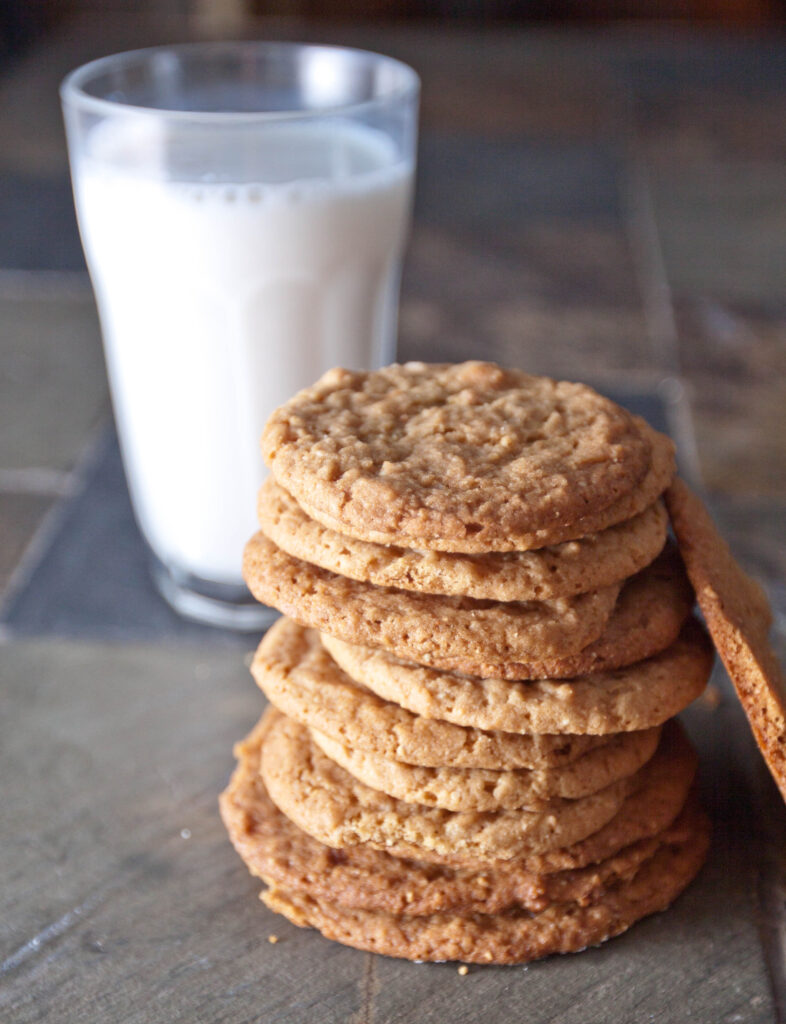 stacked peanut butter cookies in front of a glass of milk.