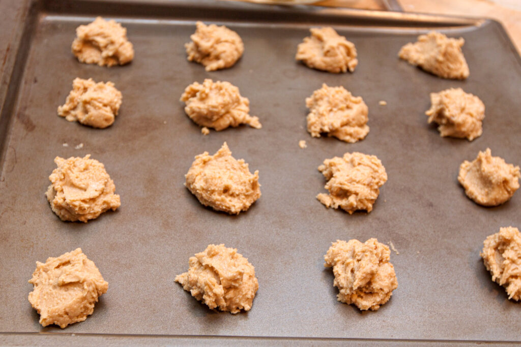 scoops of raw cookie dough on a cookie sheet.