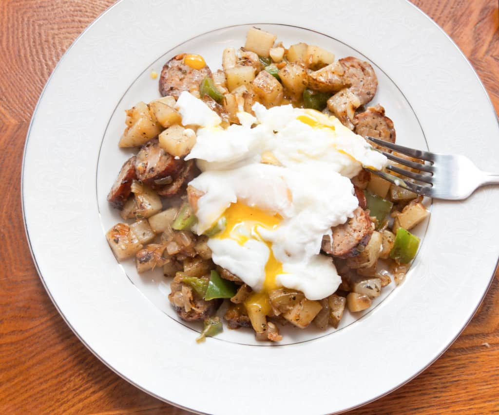 a plate with runny eggs, potaties, peppers, and sausage.
