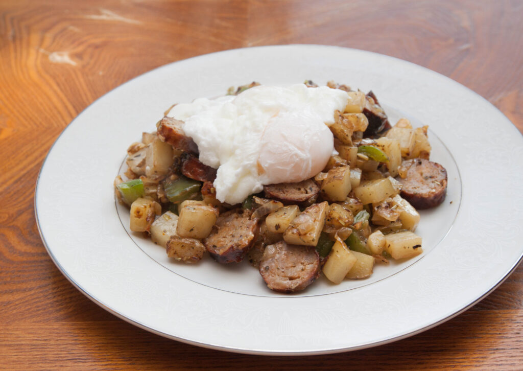 a plate of potatoes, sausage, topped with poached egg.