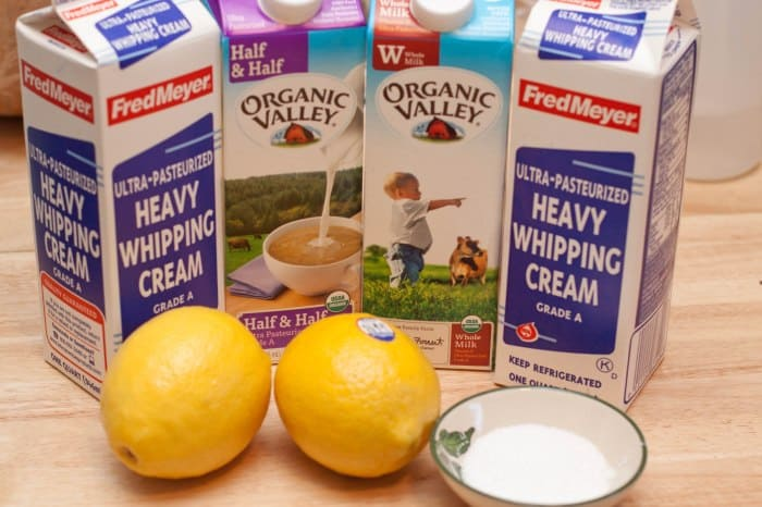 heavy whipping cream, half and half, and milk on a counter with lemons.