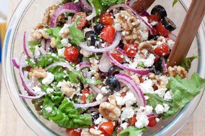 an overhead of a greek salad with walnuts.