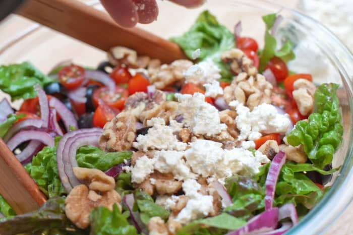 a bowl of salad topped with feta cheese.