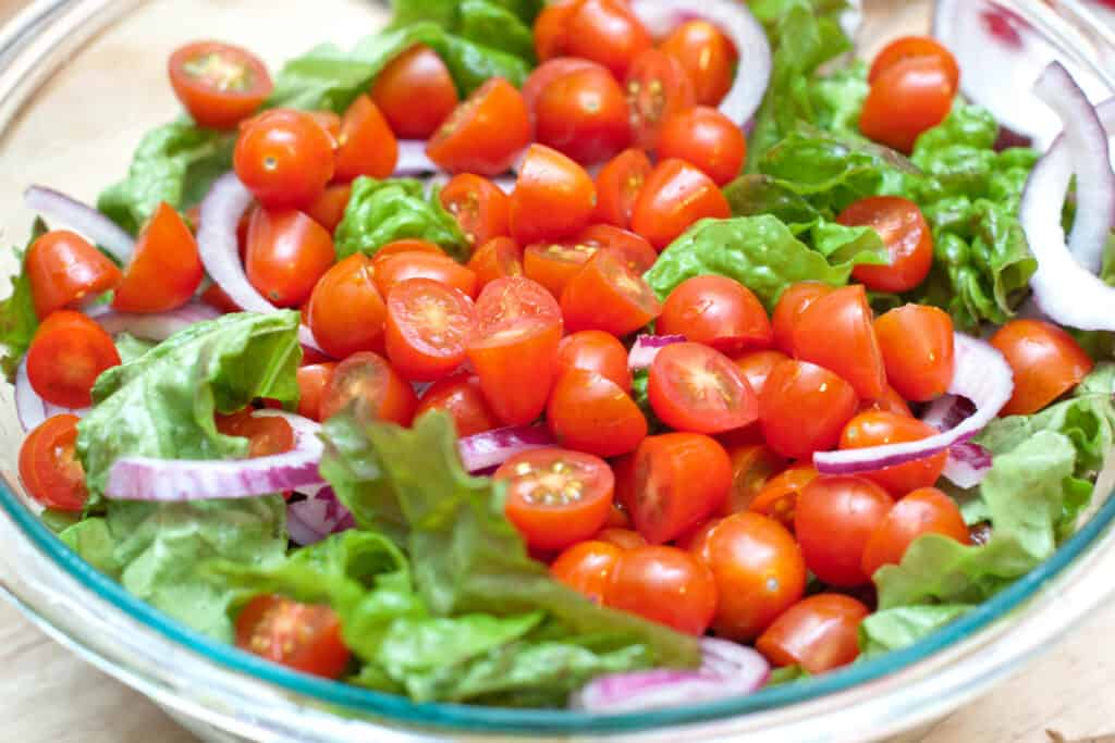 a bowl of salad greens topped with tomatoes.