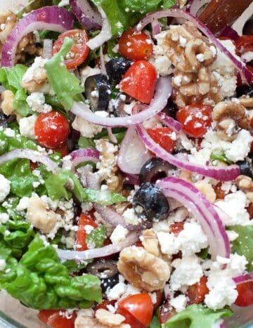 Greek-ish salad in a large bowl with tongs