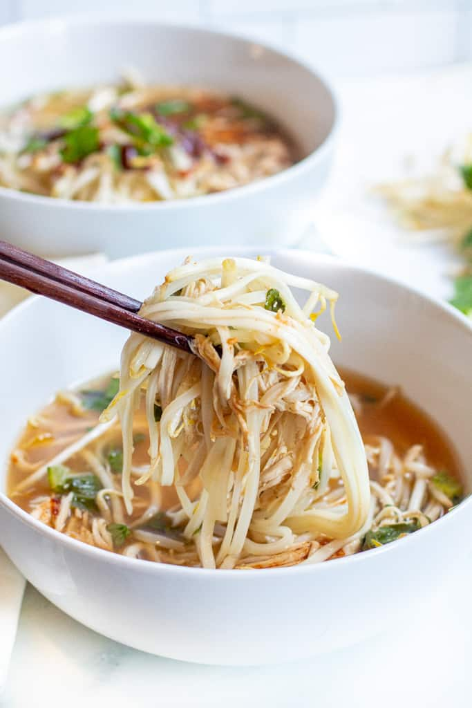 a bowl of chicken pho with chopstick holding up noodles and chicken.