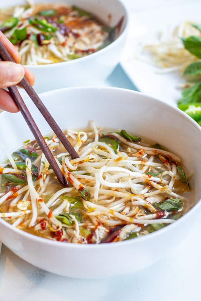 overhead of two bowls of chicken pho with chopsticks.
