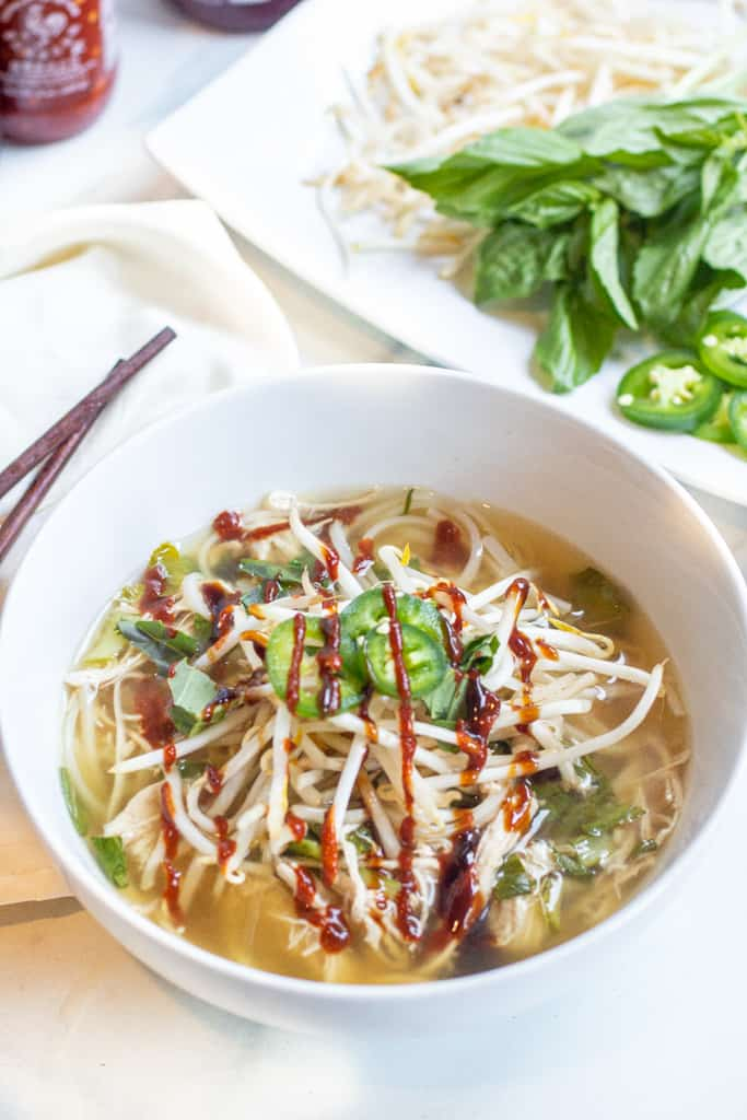 a bowl of chicken pho with sriracha, sprouts, and sliced jalapenos.