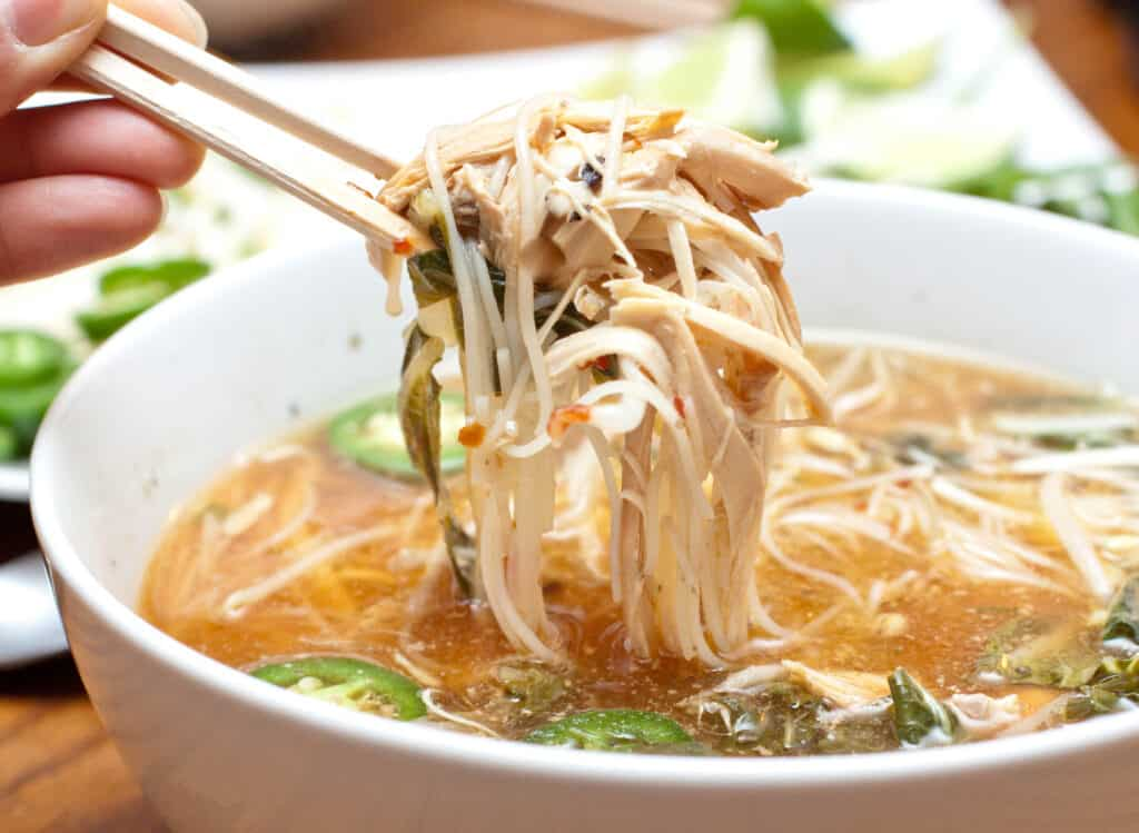 a large bowl of shredded chicken with noodles and broth and sliced jalapenos.