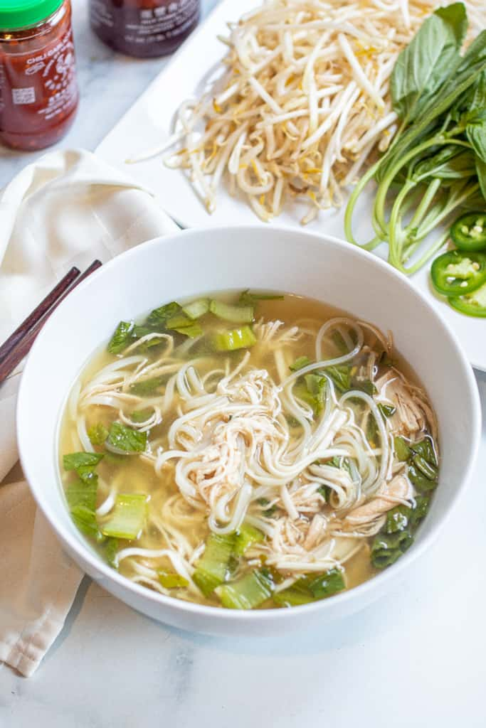 a bowl of chicken pho with noodles.