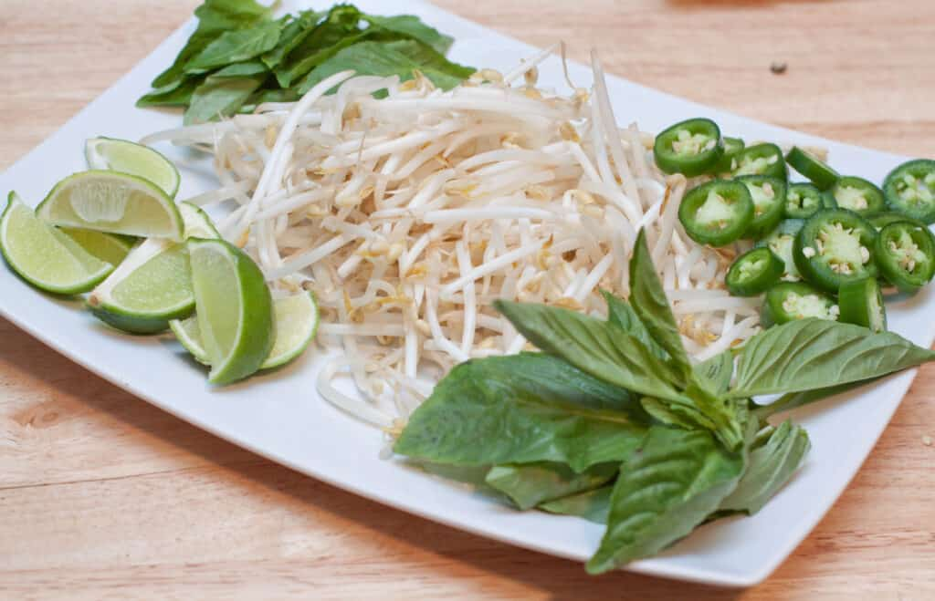 a plate of bean sprouts, sliced jalapenos, basil, and limes.
