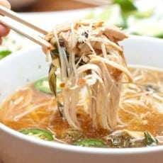 large bowl of pho with chopsticks holding up a bite