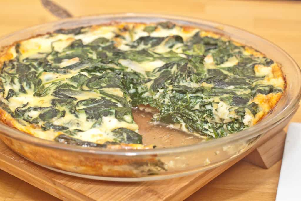 a pie dish of spinach quiche with a slice taken out