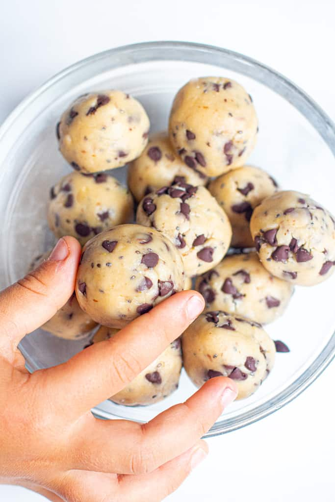 a bowl of cookie dough balls with a hand grabbing one.