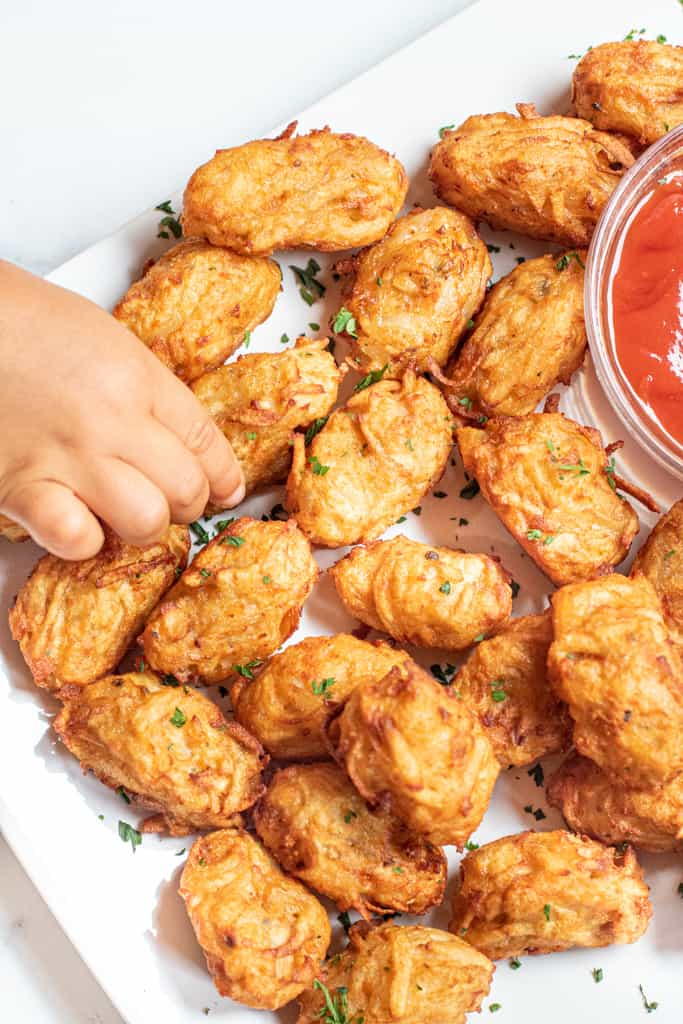 a plate of homemade tater tots with ketchup and a little hand grabbing one.