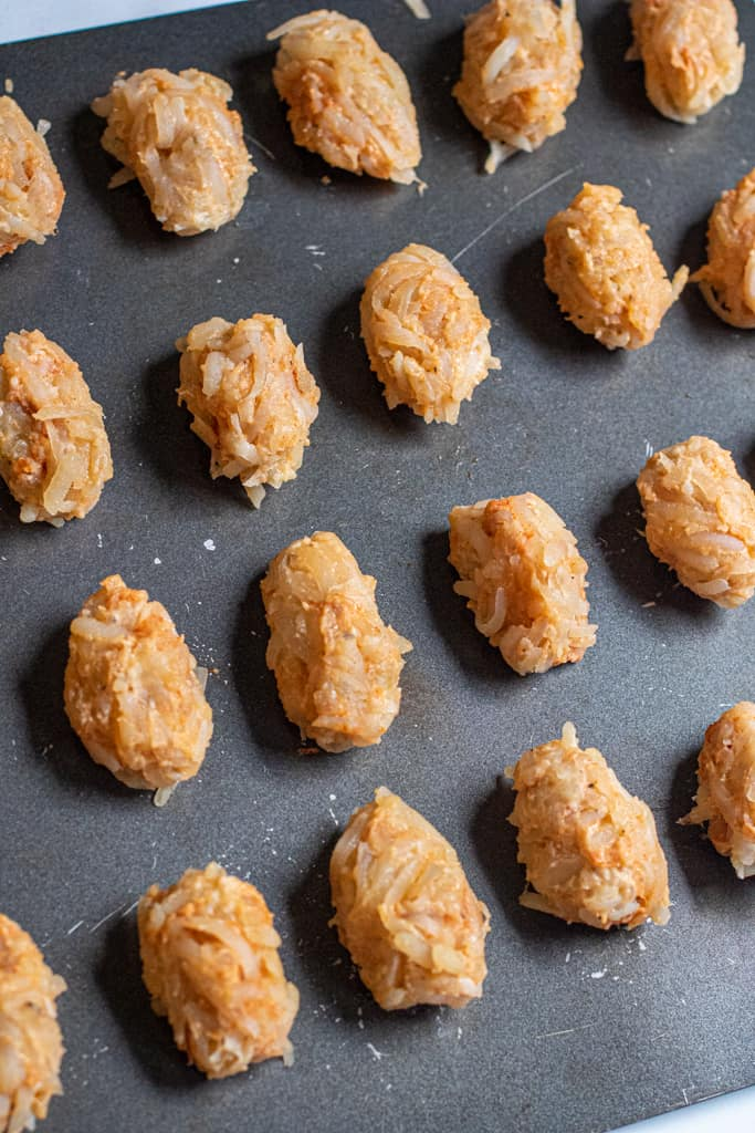 a baking sheet of formed uncooked tater tots.