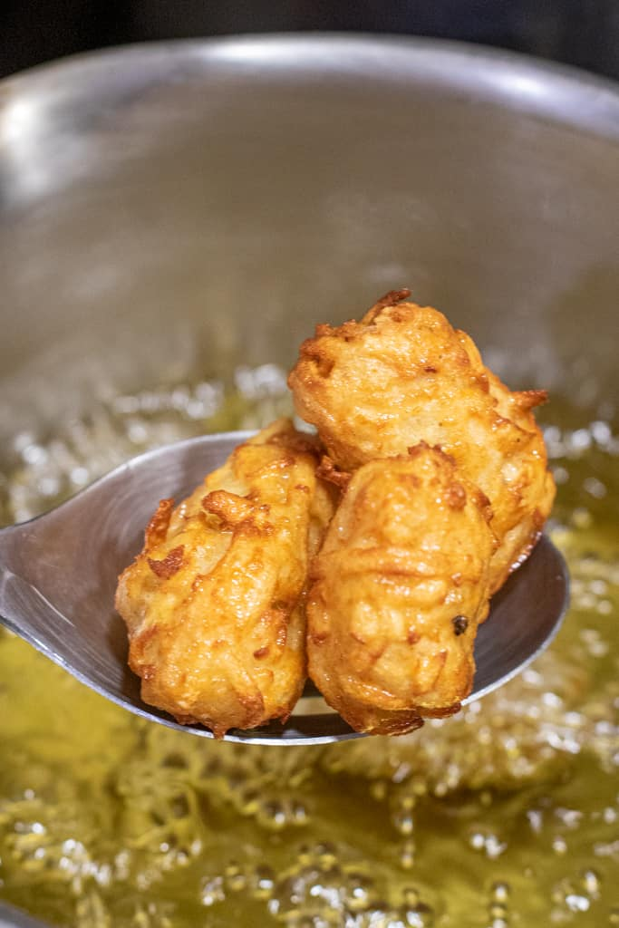 a slotted spoon holding fried tots over oil.