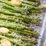 a pan of cooked asparagus with garlic and melted cheese.