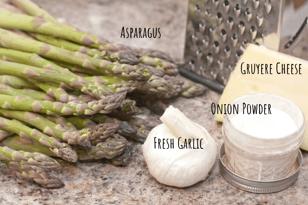raw asparagus, garlic, onion powder, gruyere, and cheese grater on counter